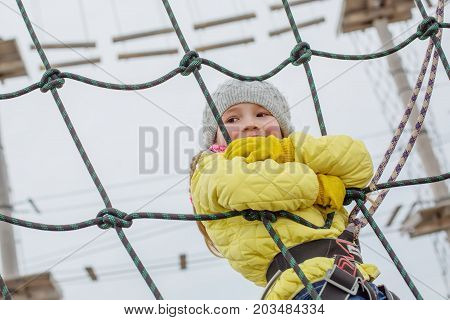 Little child on the obstacle course in the adventure park
