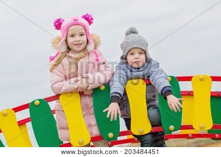 Happy little brother and sister playing in a playground in the autumn time