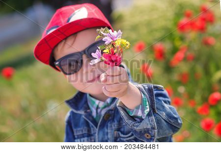 Funny little boy in sunglasses with a bouquet of wild flowers