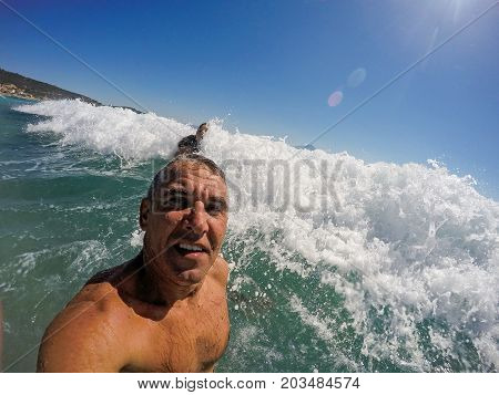 Happy Man In Big Sea Wave. Fit Middle-aged Man Standing In The Ocean.