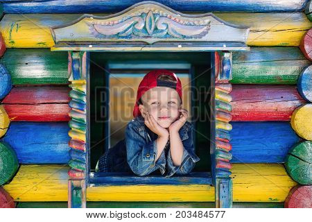 Cute little boy is playing on the playground peeking out of the window of the house