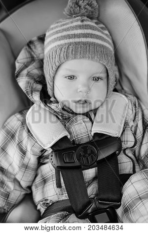 Adorable toddler boy sitting in car seat. child in winter clothes. (Black and white)