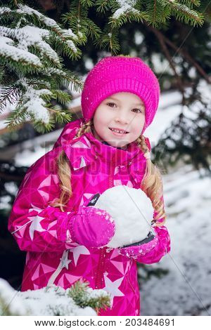 Cute little girl in a snow-covered forest sculpts a snowball