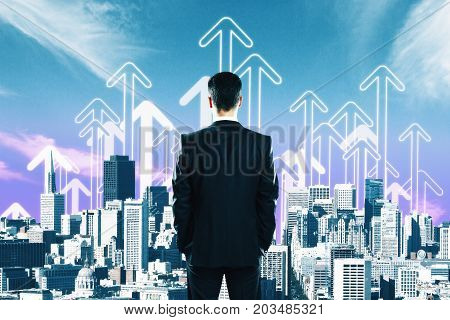 Back view of young businessman on creative city background with drawn upward arrows. Employment socncept
