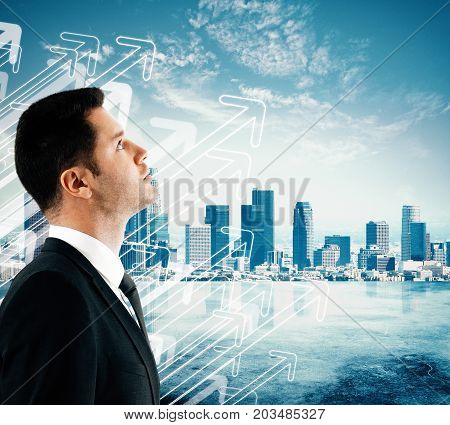 Side view of handsome young businessman on creative city background with drawn upward arrows. Executive socncept