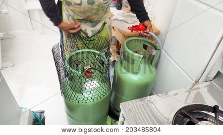 Service man to showing how to change Gas LPG tank 15 kilogram In the kitchen has stainless steel single stove.