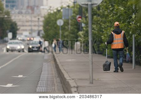 Road sweeper worker walking along city street with broom tool in Russian megapolice, rear view