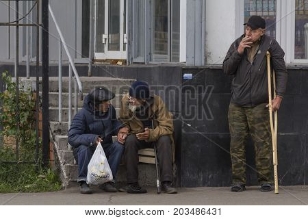 KAZAN, RUSSIA - 9 SEPTEMBER 2017: three homeless beggars men having a break near food shop, telephoto shot