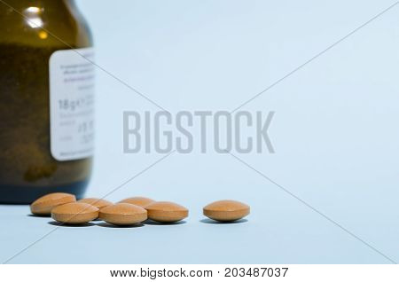 still life of pills over blue table with brown glass bottle. pharmaceutical. disease. remedy