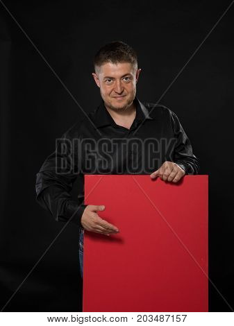 Young confident man portrait of a confident businessman showing presentation, pointing placard black background. Ideal for banners, registration forms, presentation, landings, presenting concept.