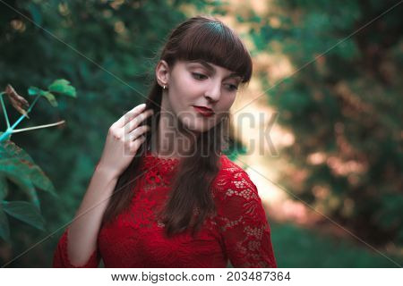 Beautiful young girl in lacy dress in autumn park