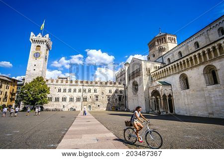 Trento Italy 14 Aug 2017 - A young woman go in bicycle in the middle of Piazza Duomo in Trento. Travel by bicycle in Italy cultural trip in Italy