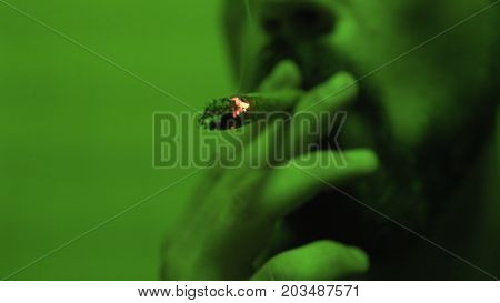 A Young Guy A Teenager Smokes A Medical Grade Of Marijuana Legalize Close-up Soft Focus. Smoking Of