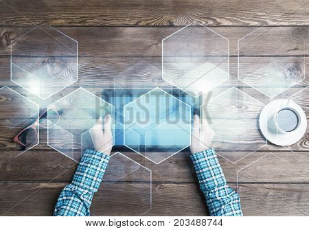 Top view of woman in checked shirt sitting at table and tablet device