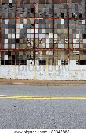 Checkerboard of broken windows and rust, vertical aspect