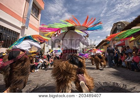 June 17 2017 Pujili Ecuador: male indigenous dancers in chaps wearing large hats dancing in the street at Corpus Christi parade