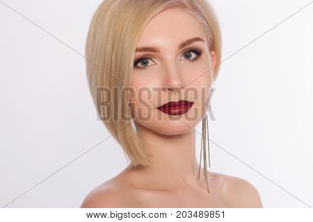 The lovely blonde with evening cosmetics on a face. Lips in style to an ombra and shooters in the eyes. Jewelry earrings. Cosmetology beauty shop fashion