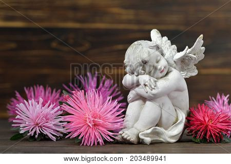 Guardian angel and flowers on wooden background
