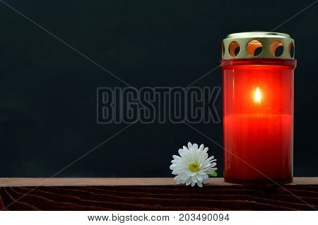 All Saints Day burning candle on dark background