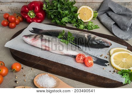 Fresh fish sea bass on wooden table.