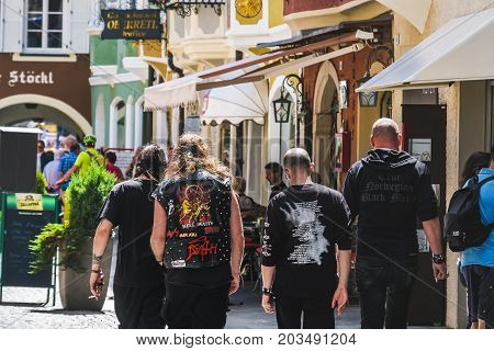 Wacken, Germany, Aug 13 2017: Heavy Metal fans metalheads walk in the street seen from behind. Alternative music lifestyle