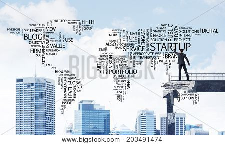 Businessman in suit writing business-related terms in form of world map while standing on broken bridge with cityscape on background. 3D rendering.