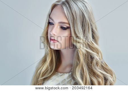 Blonde fashion  girl with long  and   shiny curly hair .  Beautiful  fashion model   with wavy hairstyle .Hair styling tousled waves