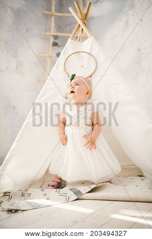 Little Girl One Year With Blue Eyes Blonde In A Lush White Dress Is Pleased And Plays In A Bright Ro