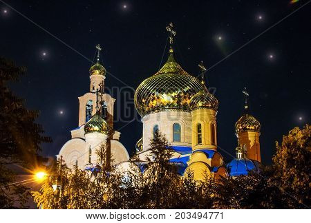 The Church of THE HOLY APOSTLES AND THE GOSPEL JOHN OF BOGHOSLOV in Pokrov city in Ukraire. Panorama of the holy Christian temple in the park at autumn night