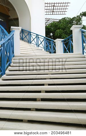 Vertical photo of white outdoors staircase with blue railing leads to the upstairs