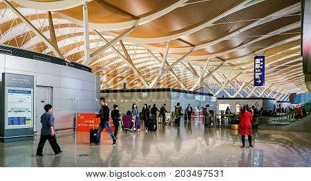 Shanghai, China - Nov 6, 2016: Interior check-in area of Shanghai Pudong International Airport. This is a modern facility. People walking about the compound.