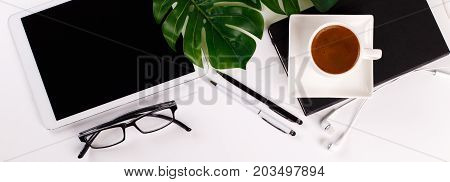 Modern white office desk table with tablet, eyeglasses, pen, pencil, ruler, monstera plant, notepad and greek cup of coffee. Top view, flat lay.Cope space