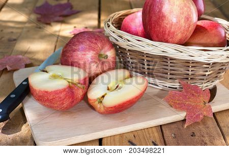 Sliced apple with other whole apples on a wood surface