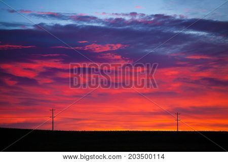 Colorful sky at sunrise with silhouetted power or telephone poles and lines
