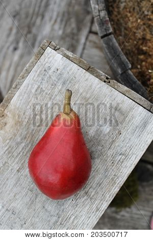 Red pear on rustic wood harvest box.