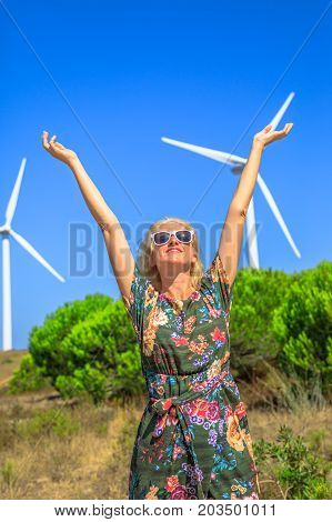 A blond caucasian woman with open arms standind in front of wind turbines rotating in Sagres, Algarve, Portugal.Alternative energy, renewable energy and environmental sustainability concept.Copy space