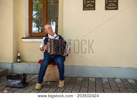 SUZDAL/ RUSSIA - AUGUST 19, 2017. An elderly man playing the russian accordion in front of the registry office. Suzdal, Russia.