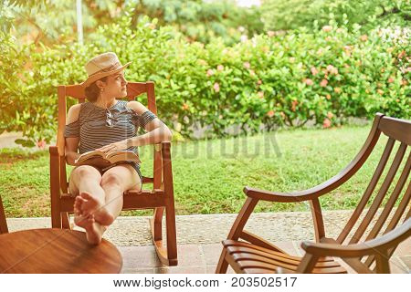 Woman with book look on side sitting on sunny summer background