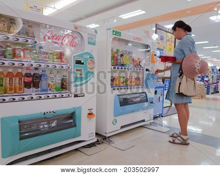 woman buys drinks in the automatic machine of Yonago Japan 08.08.2017