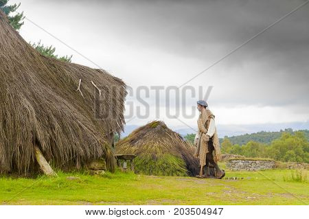 Newtonmore - august 2014: a Scottish young man is entering his hut in the highland folk museum  in this site you can find the uses and customs of the ancient Scottish and the reconstructions of their rural homes