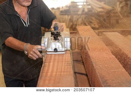Electric planer is being worked with hands of senior carpenter in carpentry workshop. Selective focus and shallow depth of field.