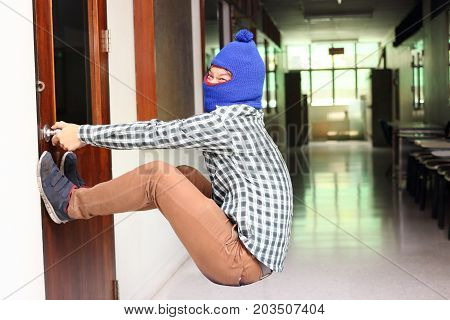 Masked burglar attempt to open the door before burglary. Criminal concept