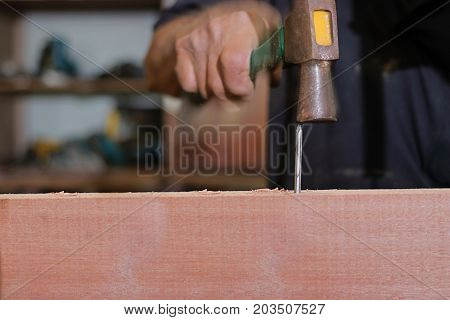 Slow speed sync of nail is hit against hammer on hand of carpenter.