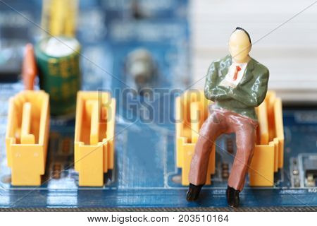 Businessman sit on a computer motherboard in concept of doing business and profiting on technology.