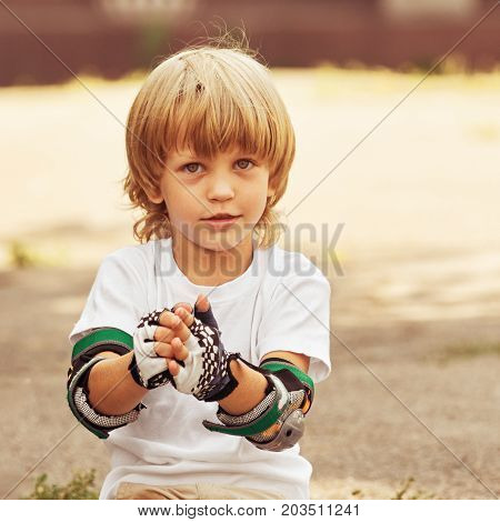 Portrait of little boy taking off gloves after rollerskating, image with toning