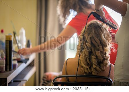 Hair stylist working on the hair of a young caucasuian lady.
