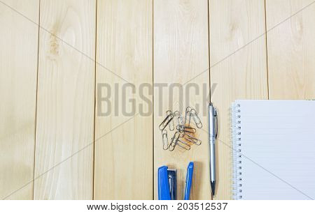 Top view of open book. Book open with stapler and pen on wooden table background
