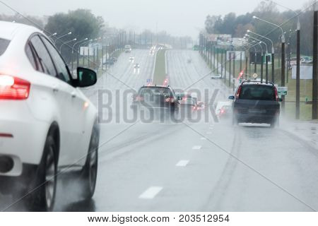 Wet Road During The Rain With Cars Riding Through Rain Puddles