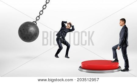 A businessman steps up on a huge floor push button to protect another man hiding from a wrecking ball. Corporate world. Business competition. Help your colleagues.
