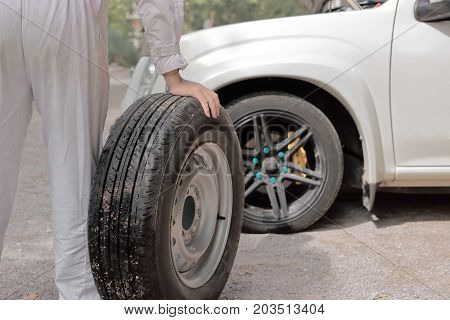 Automotive mechanic man carrying spare tire preparing change a wheel of car. Auto repair service.